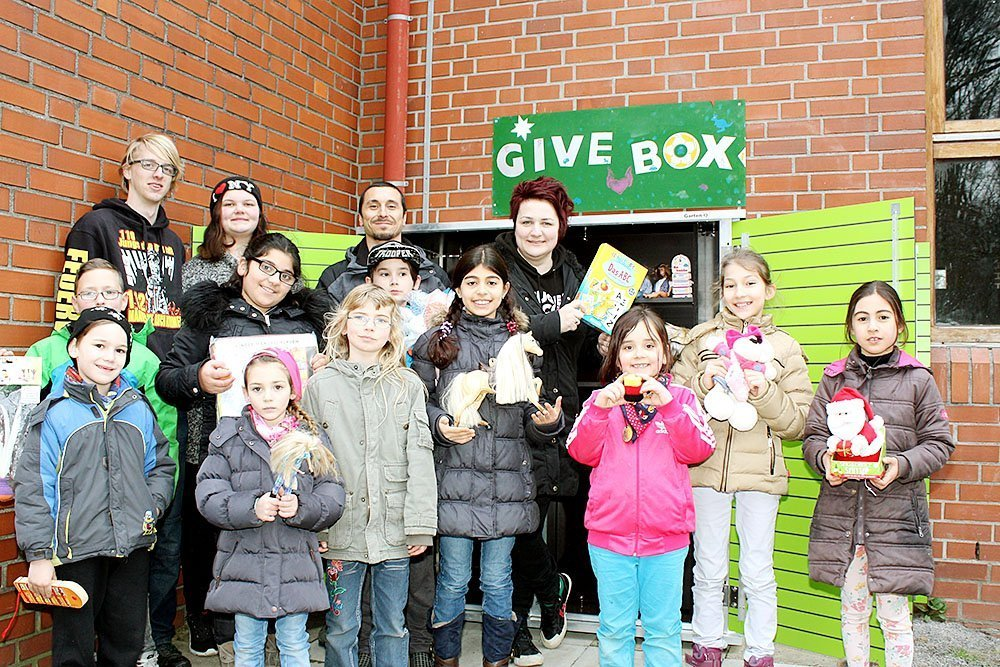 Die Leiterin derJugendfreizeitstätte Rahm Aida Demirovic-Krebs (h. r.) und ihr Stellvertreter Serkan Yoldüz (h. 2. v. r.) öffnen die Give-Box für die Kinder und Jugendlichen.