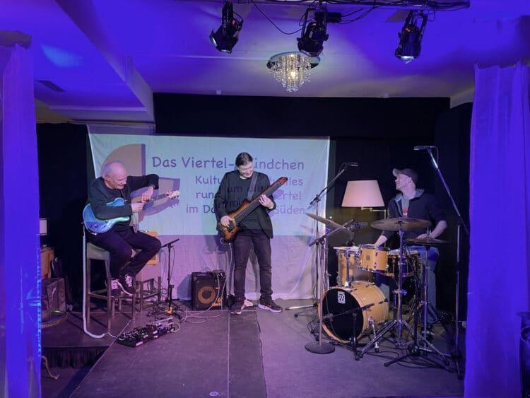 """Das Jazz-Projekt """"Pulse"""" mit Jochen Schrumpf (Gitarre), Patrik Siewert (Bass) und Wilm Flinks (Schlagzeug, v. l.) auf der Bühne im Wohnzimmer am Piepenstock. (Foto: UnARt)"""