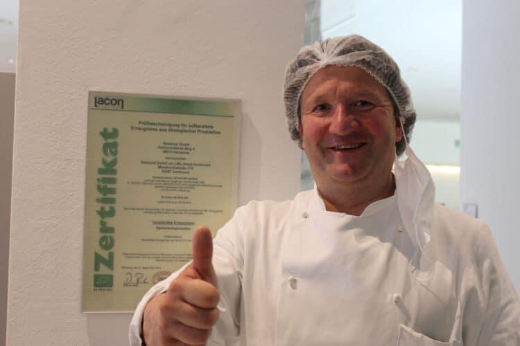 """Küchenchef Matthias Ehrenschneider vor der """"Prüfbescheinigung für aufbereitete Erzeugnisse aus ökologischer Produktion"""" eines Instituts für Lebensmittelzertifizierung. (Foto: LWL/Herstell)"""